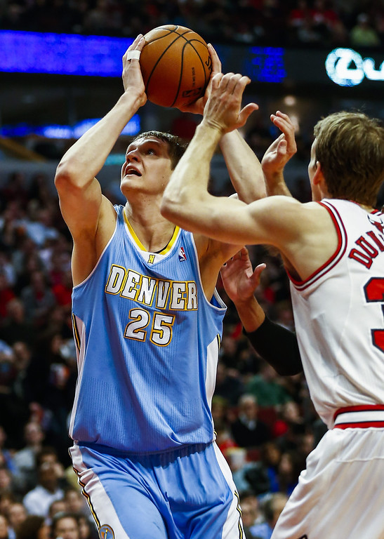 . Denver Nuggets center Timofey Mozgov of Russia (L) eyes the basket as he attempts a shot in front of Chicago Bulls forward Mike Dunleavy (R) in the first half of their NBA game at the United Center in Chicago, Illinois, USA, 21 February 2014  EPA/TANNEN MAURY