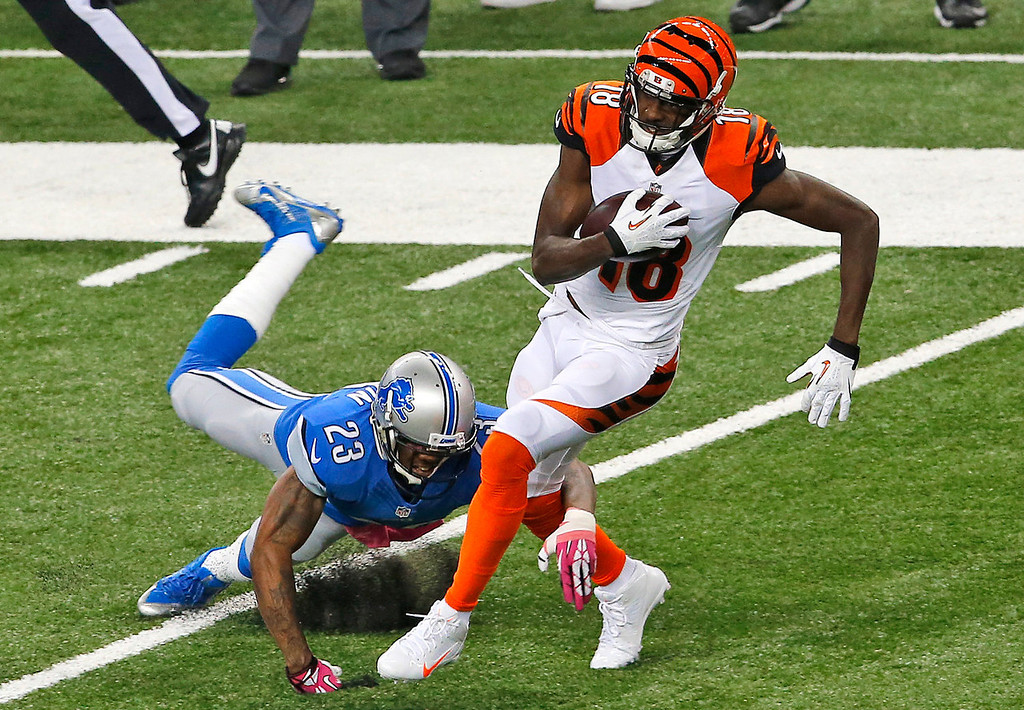 . Cincinnati Bengals wide receiver A.J. Green (18) breaks the tackle of Detroit Lions cornerback Chris Houston (23) on an 82-yard touchdown reception in the first quarter of an NFL football game  Sunday, Oct. 20, 2013, in Detroit. (AP Photo/Paul Sancya)