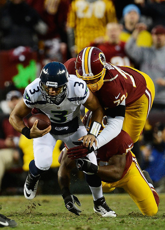 . Russell Wilson #3 of the Seattle Seahawks is sacked by   Trent Williams #71 of the Washington Redskins during the NFC Wild Card Playoff Game at FedExField on January 6, 2013 in Landover, Maryland.  (Photo by Patrick McDermott/Getty Images)