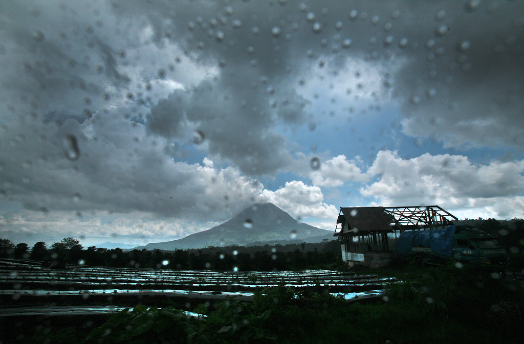 . Mount Sinabung is seen from inside a car after a rain in Dalan Jahe, North Sumatra, Indonesia, Monday, Nov. 25, 2013. Powerful bursts of hot ash and gravel erupted from the rumbling volcano in western Indonesia Monday, a day after authorities had raised the volcano\'s alert status to the highest level. (AP Photo/Binsar Bakkara)