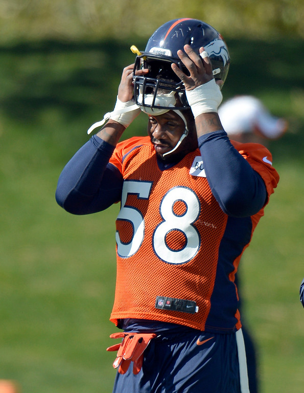 . Denver Broncos outside linebacker Von Miller (58) puts on his helmet during his first day back to practice October 16, 2013 at Dove Valley. Miller just finished serving a six game suspension. (Photo by John Leyba/The Denver Post)