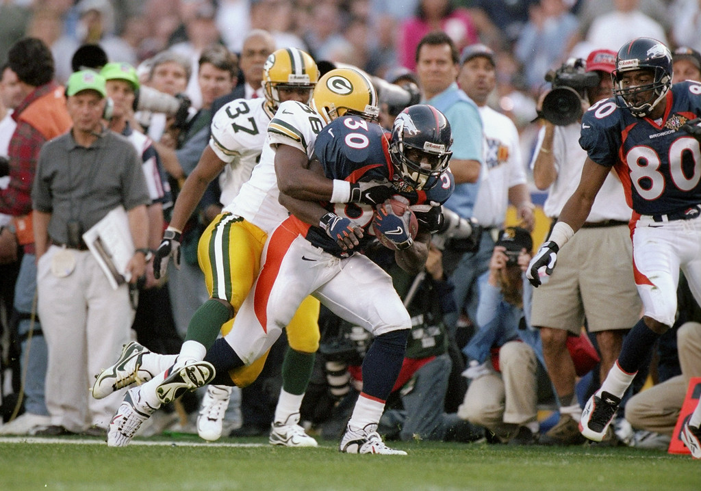 . Terrell Davis #30 of the Denver Broncos is tackeled by Leroy Butler #36 and Tyrone Williams #37 of the Green Bay Packers during Super Bowl  XXXII at Qualcomm Stadium in San Diego, California.  (Andy Lyons/Allsport)