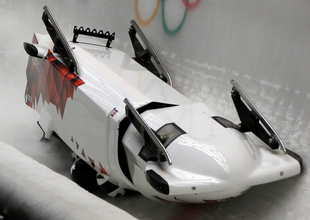 . The team from Canada CAN-3, with Justin Kripps, Jesse Lumsden, Cody Sorensen and Ben Coakwell, slide down the track upside down after crashing in turn sixteen during the men\'s four-man bobsled competition at the 2014 Winter Olympics, Saturday, Feb. 22, 2014, in Krasnaya Polyana, Russia. (AP Photo/Dita Alangkara)