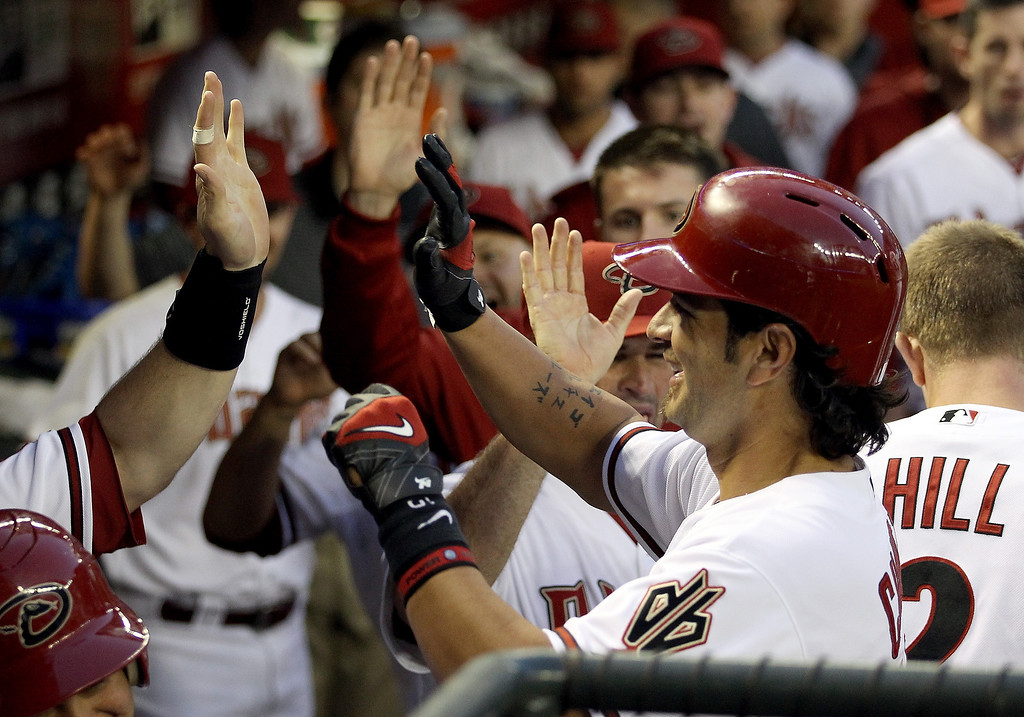 . Eric Chavez #12 of the Arizona Diamondbacks high fives teammates in the dugout after scoring a second inning run against the Colorado Rockies during the MLB game at Chase Field on April 29, 2014 in Phoenix, Arizona.  (Photo by Christian Petersen/Getty Images)