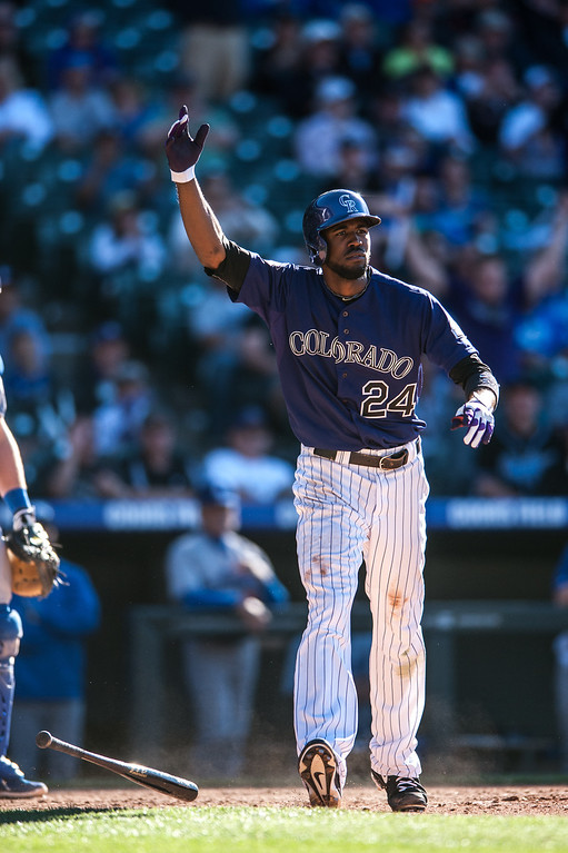 . DENVER, CO - JUNE 1:  Dexter Fowler #24 of the Colorado Rockies begins to celebrate after hitting what would be the game-winning RBI single in the 10th inning of a game against the Los Angeles Dodgers at Coors Field on June 1, 2013 in Denver, Colorado. The Rockies beat the Dodgers 7-6 in 10 innings. (Photo by Dustin Bradford/Getty Images)