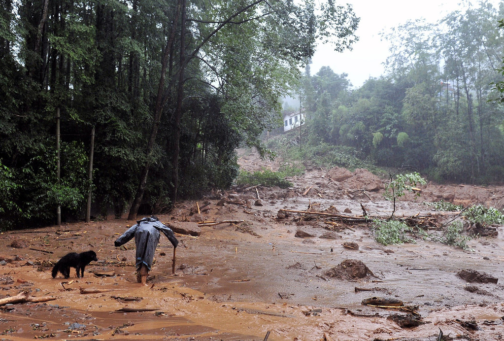 . A local resident walks with a dog after a landslide triggered by heavy rainstorm hit Shanxi village of Zhongxing township in Dujiangyan, southwest China\'s Sichuan province on July 10, 2013.  Between 30 and 40 people were buried by a landslide in southwest China on July 10 local officials said, as heavy rains in the area also destroyed homes and bridges.   STR/AFP/Getty Images