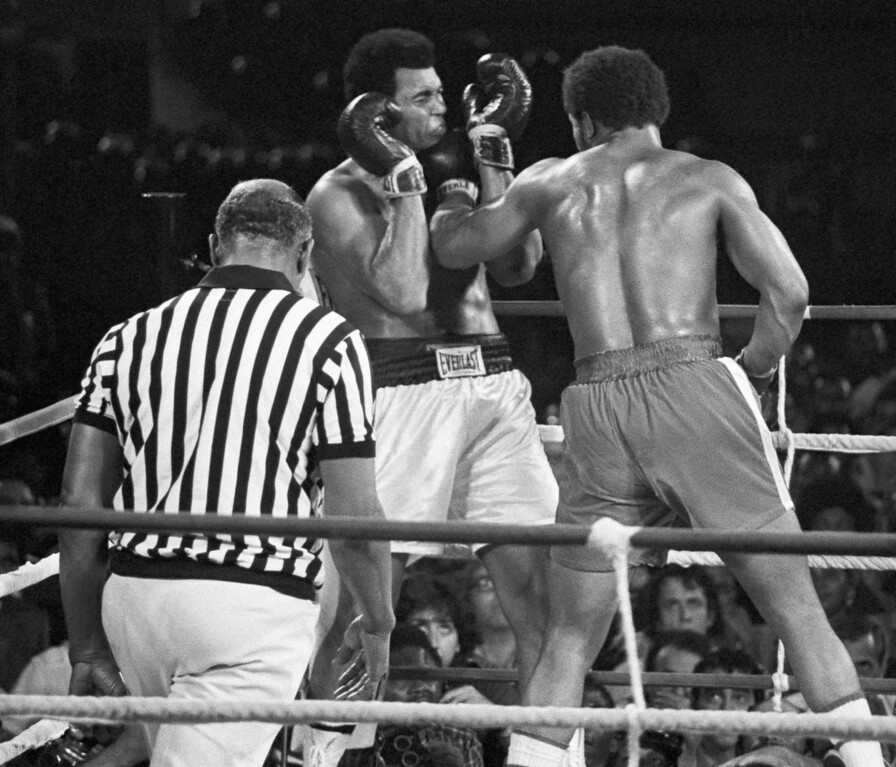. Boxer Muhammad Ali winces as he takes a George Foreman left to the jaw in fifth round of their heavyweight championship bout in Kinshasa, Zaire, October 30, 1974.   Referee Zack Clayton watches.   Ali knocked out Foreman in the eighth round to regain the title.   (AP Photo/Ed Kolenovsky)