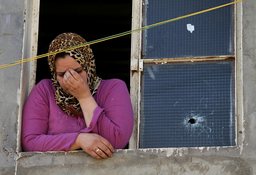 . A Lebanese woman reacts after her home was damaged from a bullet during clashes that erupted between supporters and opponents of Syrian President Bashar Assad, near the Sunni neighborhood of Tariq Jadideh, in Beirut, Lebanon, Sunday, March 23, 2014. Syria-related clashes between supporters and opponents of Syrian President Bashar Assad have prompted Lebanese troops to deploy to a Beirut neighborhood to calm tensions. The Army deployment came after rival Sunni gunmen exchanged gunfire and rocket-propelled-grenades for several hours in the area, in the worst fighting in the Lebanese capital in nearly two years. (AP Photo/Hussein Malla)
