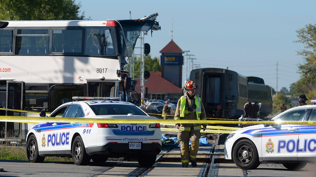 . A firefighter surveys the scene of a collision with a train and a city bus in Ottawa, Ontario, Wednesday, Sept. 18, 2013.  An Ottawa Fire spokesman said there are ìmultiple fatalitiesî and a number of people injured from the bus. (AP Photo/The Canadian Press, Adrian Wyld)