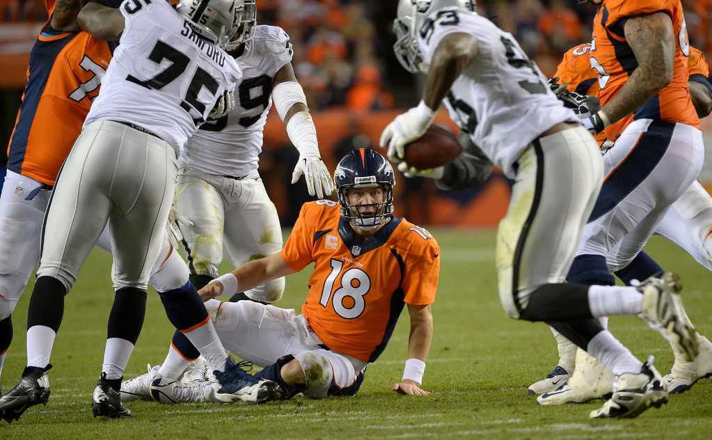 . DENVER, CO - SEPTEMBER 23: Denver Broncos quarterback Peyton Manning (18) on the turf watches Oakland Raiders defensive end Jason Hunter (93) run away with the ball after fumbling during the fourth quarter. The Broncos would win 37-21. The Denver Broncos took on the Oakland Raiders at Sports Authority Field at Mile High in Denver on September 23, 2013. (Photo by Joe Amon/The Denver Post)