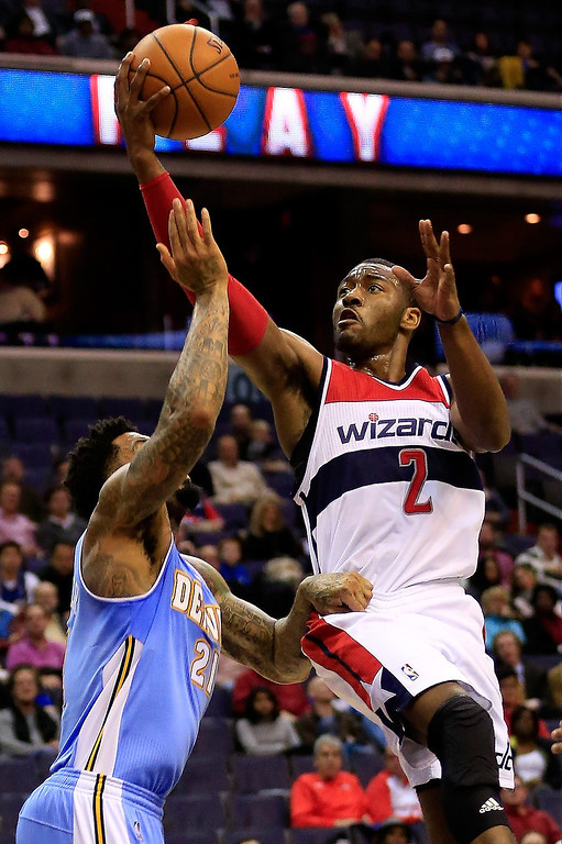 . John Wall #2 of the Washington Wizards puts up a shot in front of Wilson Chandler #21 of the Denver Nuggets during the first half at Verizon Center on December 9, 2013 in Washington, DC.   (Photo by Rob Carr/Getty Images)