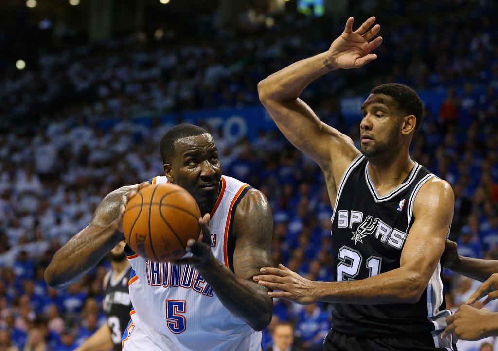 . OKLAHOMA CITY, OK - MAY 27: Kendrick Perkins #5 of the Oklahoma City Thunder handles the ball against Tim Duncan #21 of the San Antonio Spurs in the third quarter during Game Four of the Western Conference Finals of the 2014 NBA Playoffs at Chesapeake Energy Arena on May 27, 2014 in Oklahoma City, Oklahoma. (Photo by Ronald Martinez/Getty Images)