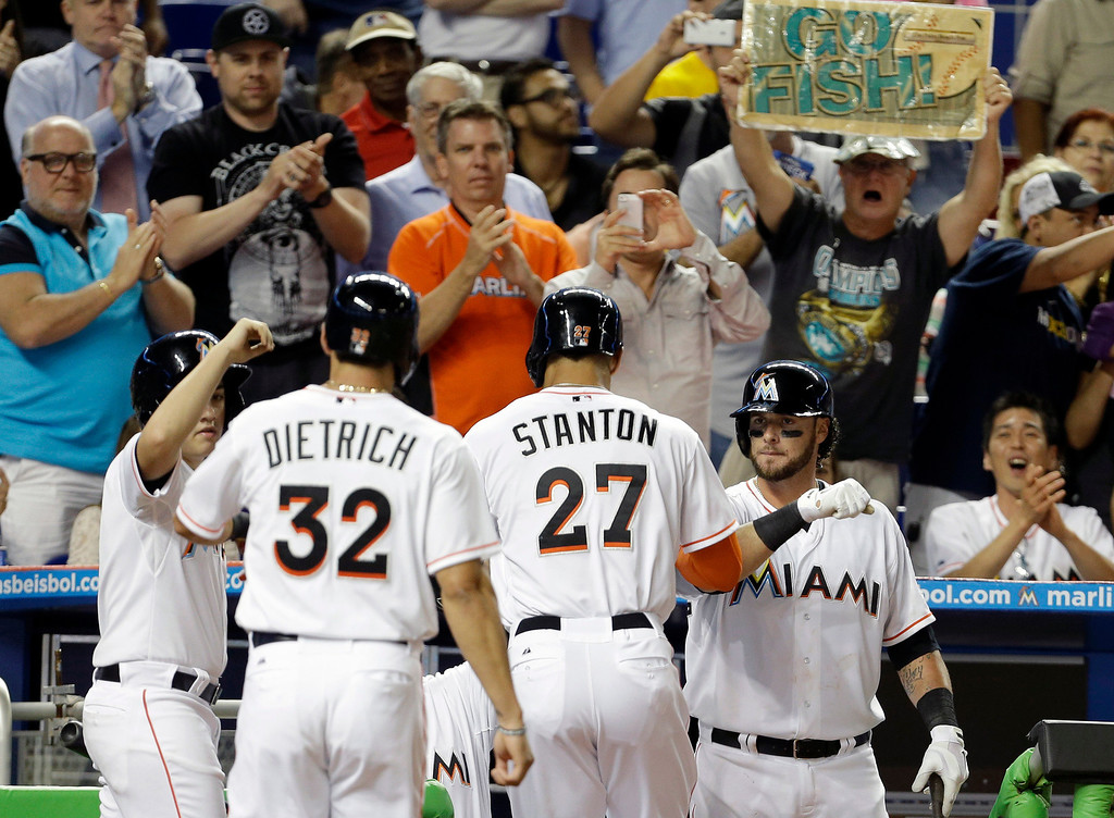 . Miami Marlins\' Giancarlo Stanton (27) and Derek Dietrich (32) are met by teammate Jarrod Saltalamacchia, right, after Stanton hit a two-run home run in the sixth inning of a baseball game against the Colorado Rockies, Wednesday, April 2, 2014, in Miami. The Rockies defeated the Marlins 6-5. (AP Photo/Lynne Sladky)