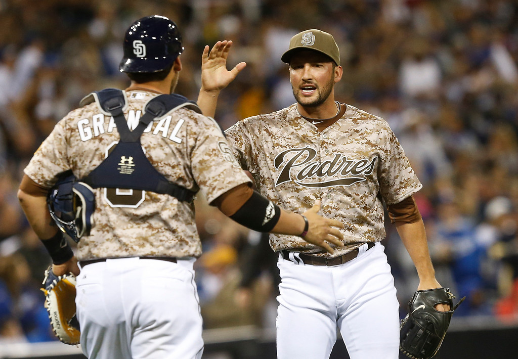 . San Diego Padres closer Huston Street  and catcher Yasmani Grandal congratulate each other after the Padres\' 3-1 victory over the Los Angeles Dodgers in the seventh inning of the opening game of Major League baseball in the United States Sunday, March 30, 2014, in San Diego.  (AP Photo/Lenny Ignelzi)