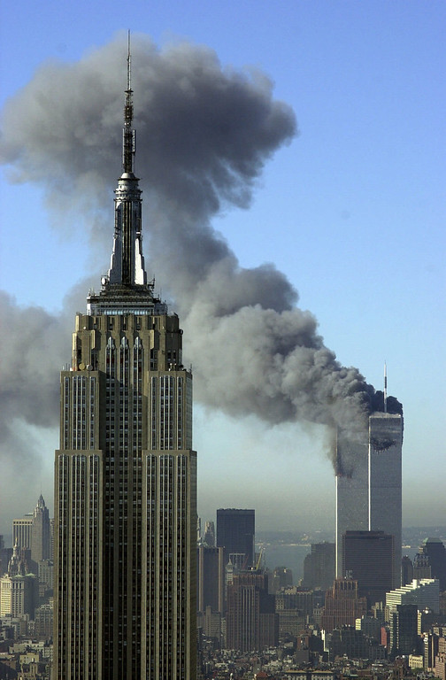 . CRIME TERRORISM WORLD TRADE CENTER TWIN TOWERS BURNING TERRORIST ATTACK BLACK SMOKE EMPIRE STATE BUILDING SKYLINE SKYSCRAPERS OVERALL GENERAL VIEW