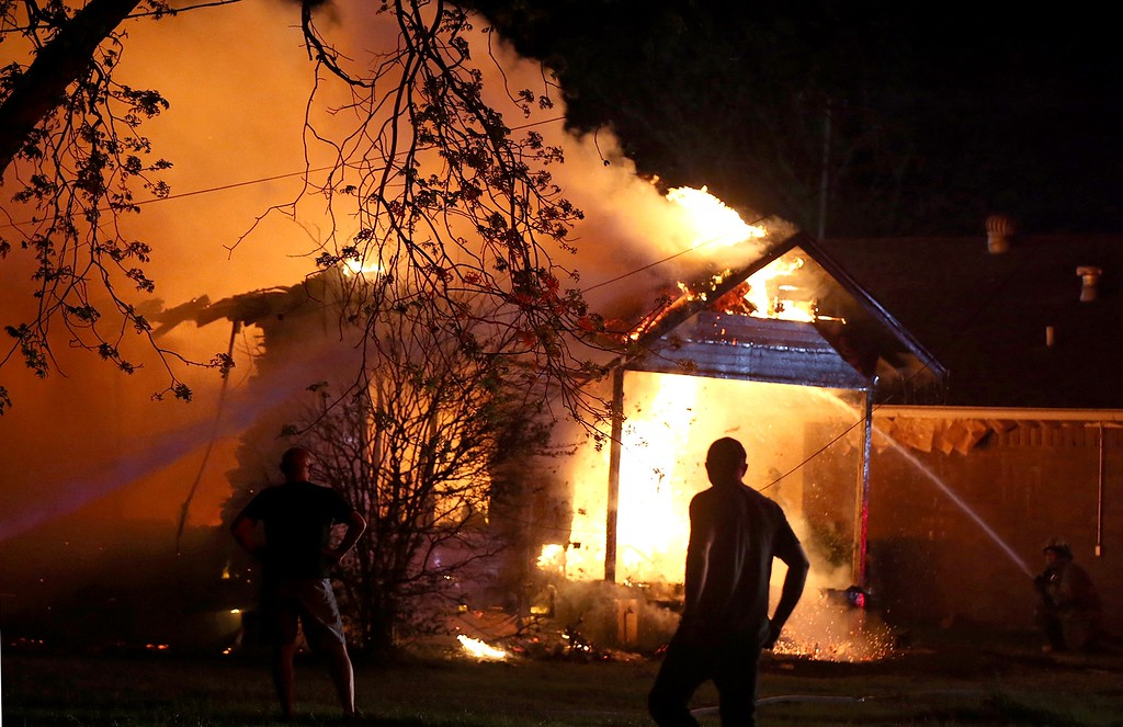 . A person looks on as emergency workers fight a house fire after a near by fertilizer plant exploded Wednesday, April 17, 2013, in West, Texas. (AP Photo/ Waco Tribune Herald, Rod Aydelotte)