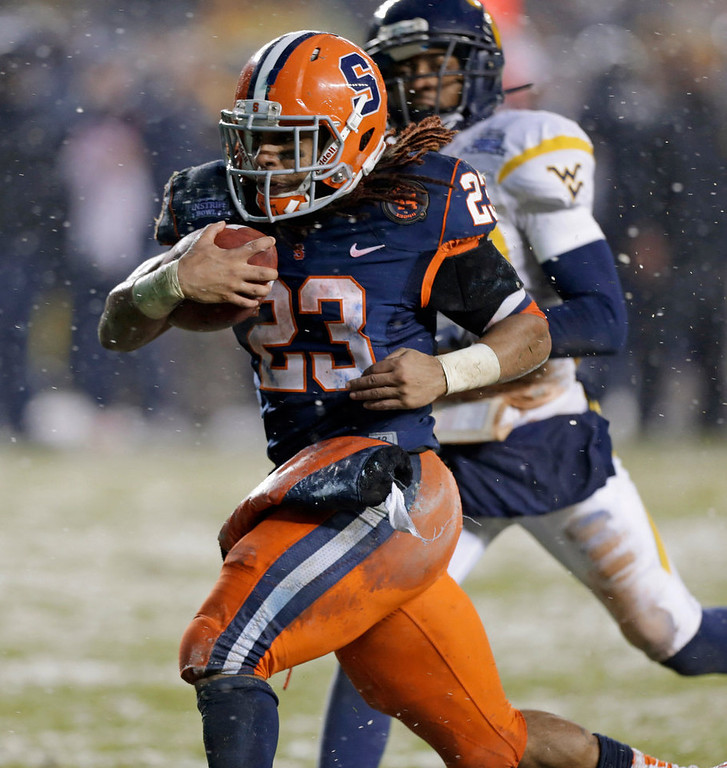 . With West Virginia cornerback Pat Miller, rear, in pursuit, Syracuse running back Prince-Tyson Gulley (23) heads for the end zone for a second-quarter touchdown in the Pinstripe Bowl NCAA college football game at Yankee Stadium in New York, Saturday, Dec. 29, 2012. (AP Photo/Kathy Willens)