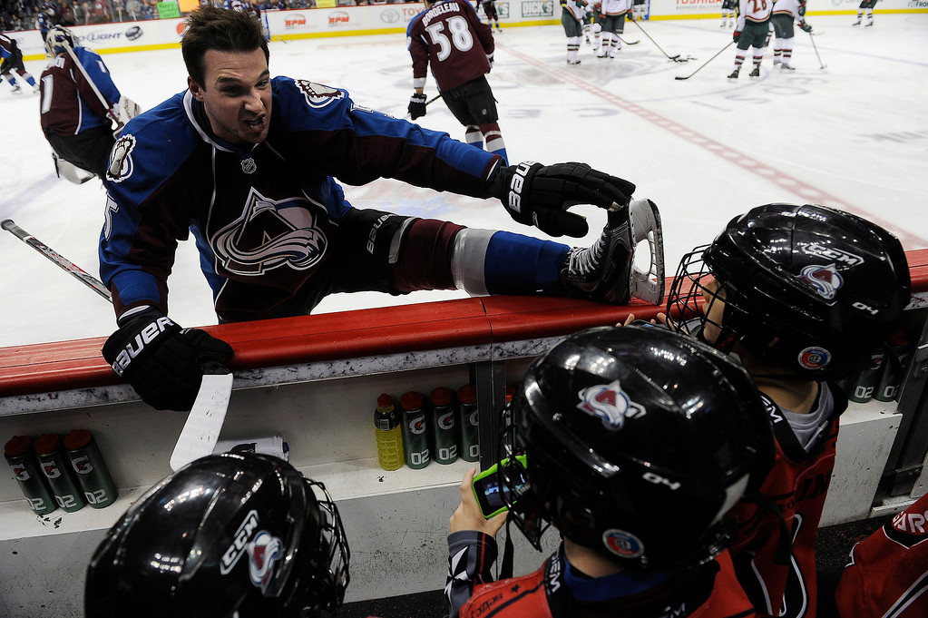 . Shane O\'Brien (5) of the Colorado Avalanche chats with young fans on the bench as he stretches during warm ups prior to their game against the Minnesota Wild on Saturday, April 27, 2012 at Pepsi Center. Seth A. McConnell, The Denver Post