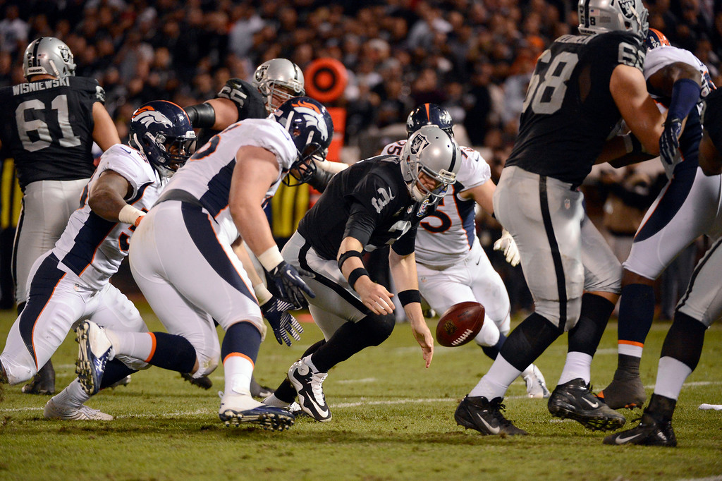 . Oakland Raiders quarterback Carson Palmer (3) fumbles the ball and was recovered by Denver Broncos defensive tackle Mitch Unrein (96) during the third quarter Thursday, December 6, 2012 during Thursday Night Football at O.c Coliseum in Oakland  John Leyba, The Denver Post