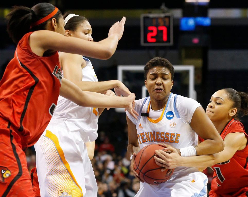 . Tennessee guard Kamiko Williams (4) has the ball knocked away by Louisville guard Bria Smith, right, as she drives to the basket in front of teammate Jasmine Jones and Louisville center Sheronne Vails, left, in the first half of the regional final in the NCAA women\'s college basketball tournament in Oklahoma City, Tuesday, April 2, 2013.  (AP Photo/Sue Ogrocki)