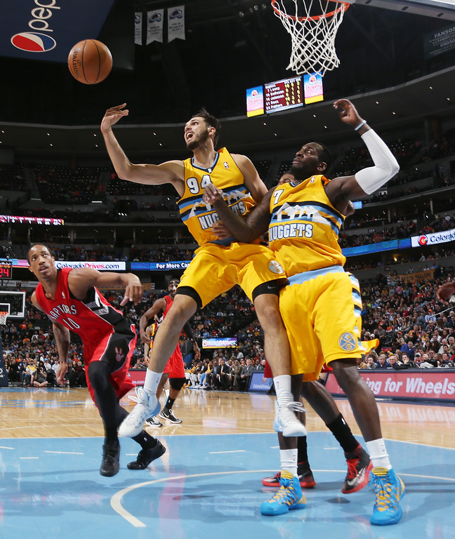. Denver Nuggets guard Evan Fournier, center, of France, reaches out for loose ball as forward J.J. Hickson, right, and Toronto Raptors guard DeMar DeRozan, left, cover in the third quarter of an NBA basketball game in Denver, Friday, Jan. 31, 2014. (AP Photo/David Zalubowski)