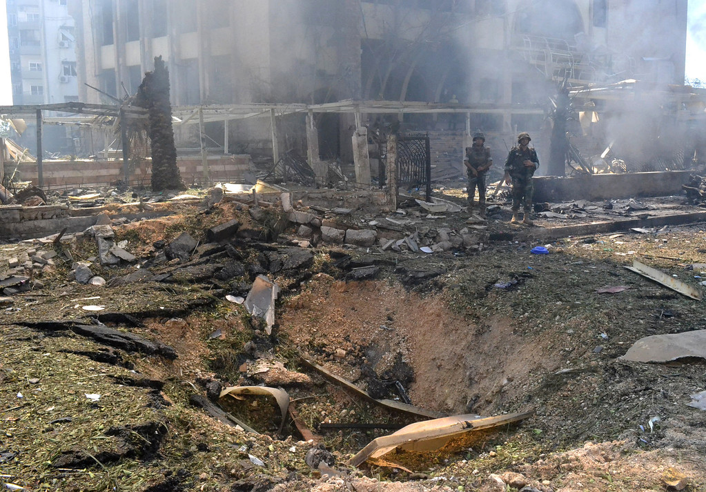 . Lebanese army soldiers stand next to a blast crater outside of a mosque, in the northern city of Tripoli, Lebanon, Friday Aug. 23, 2013. (AP Photo)