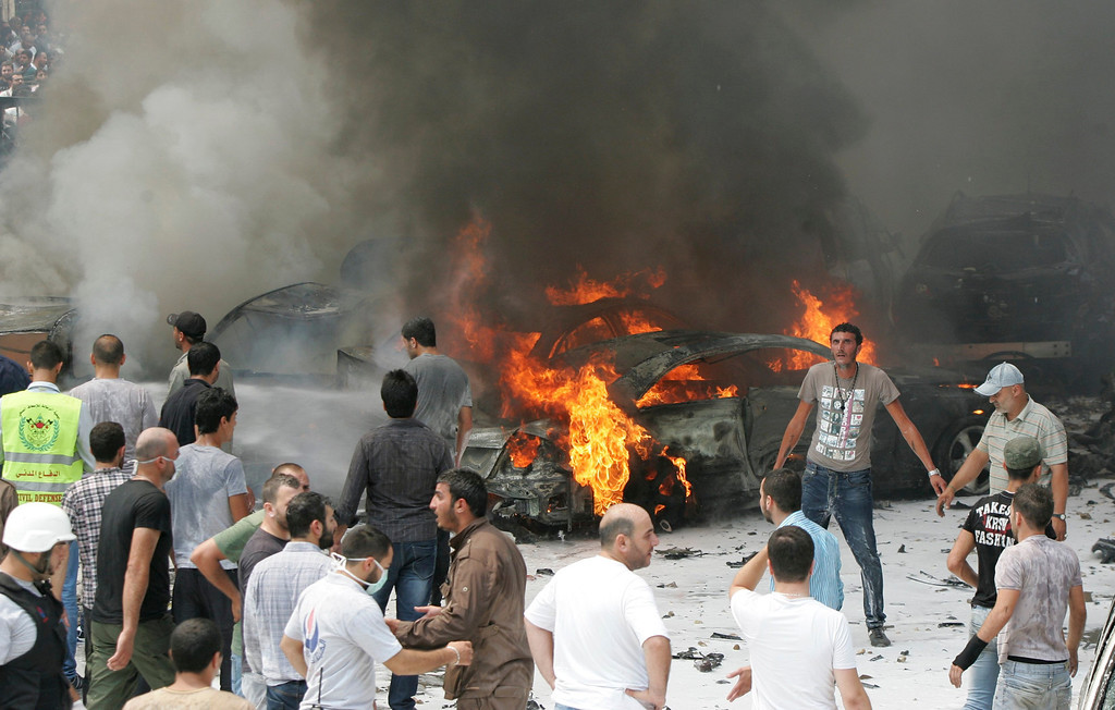 . Civil Defense members and residents gather at the site of an explosion in Beirut\'s southern suburbs July 9, 2013.  REUTERS/Issam Kobeisy