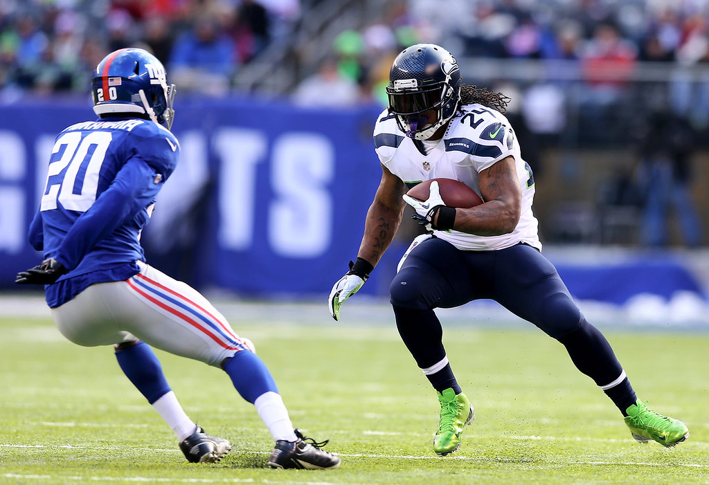 . Marshawn Lynch #24 of the Seattle Seahawks carries the ball as  Prince Amukamara #20 of the New York Giants defends at MetLife Stadium on December 15, 2013 in East Rutherford, New Jersey.  (Photo by Elsa/Getty Images)