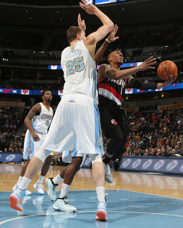 . Denver Nuggets center Timofey Mozgov, left, of Russia, fouls Portland Trail Blazers guard Damian Lillard as he drives the lane for a shot in the first quarter of an NBA basketball game in Denver, Tuesday, Feb. 25, 2014. (AP Photo/David Zalubowski)
