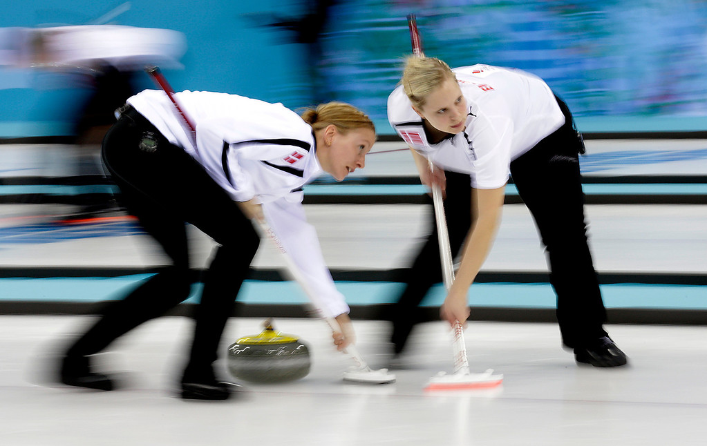 . Denmark\'s Helle Simonsen, left, and Jeanne Ellegaard, right, sweep the ice during the women\'s curling competition against Canada at the 2014 Winter Olympics, Thursday, Feb. 13, 2014, in Sochi, Russia. (AP Photo/Wong Maye-E)
