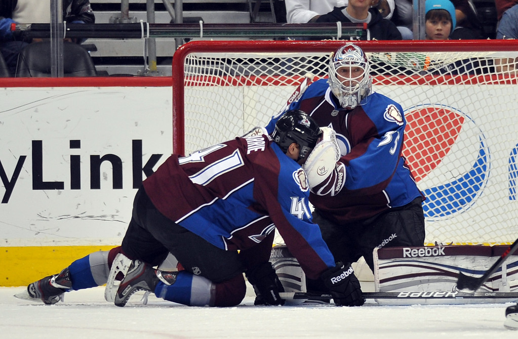 . DENVER, CO. - APRIL 13 : Goalie Jean-Sebastien Giguere of Colorado Avalanche (35) helps his teammate Tyson Barrie (41) stand during the 1st period of the game against Vancouver Canucks at Pepsi Center. Denver, Colorado. April 13, 2013. (Photo By Hyoung Chang/The Denver Post)
