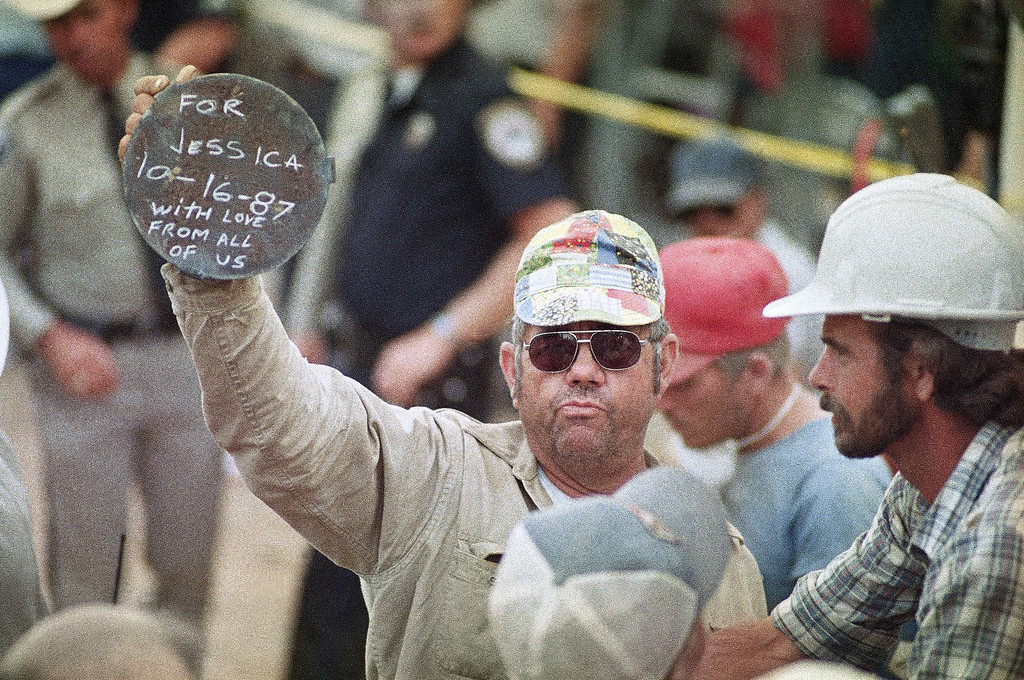 . A craftsman proudly displays the gift which he created for 18-month-old Jessica McClure who was successfully rescued from a 22-foot (6.7 meter) underground abandoned water well in Midland, Texas, Oct. 17, 1987. The metal cover will be placed over the opening in the ground where Jessica fell in. (AP Photo/Eric Gay)