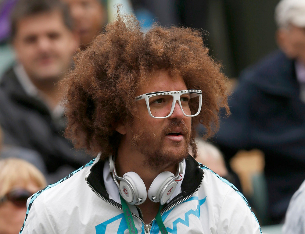. Stefan Kendal Gordy, known as Redfoo, of the band LMFAO, watches his girlfriend Victoria Azarenka of Belarus after she defeated Maria Joao Koehler of Portugal in their women\'s singles tennis match at  the Wimbledon Tennis Championships, in London June 24, 2013.  REUTERS/Eddie Keogh