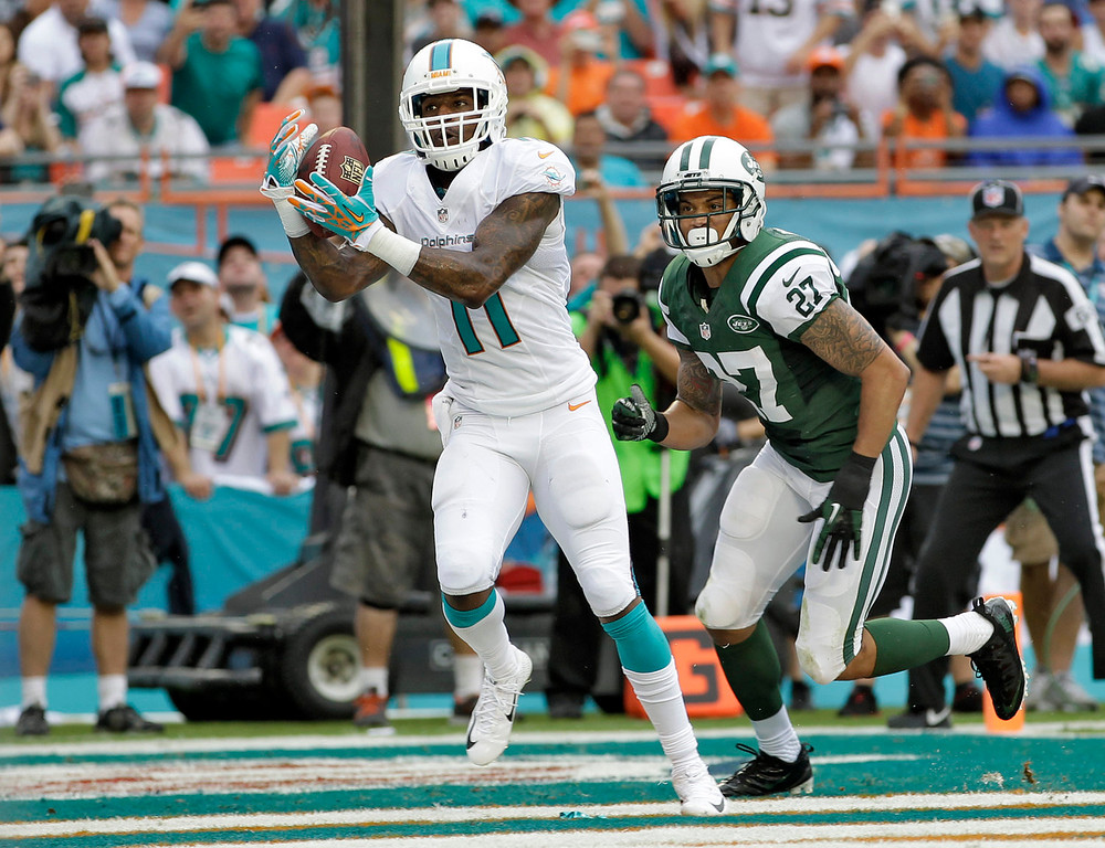 . Miami Dolphins wide receiver Mike Wallace (11) pulls in a 5-yard touchdown pass in front of New York Jets cornerback Dee Milliner (27) during the second quarter of an NFL football game on Sunday, Dec. 29, 2013, in Miami Gardens, Fla. (AP Photo/Alan Diaz)