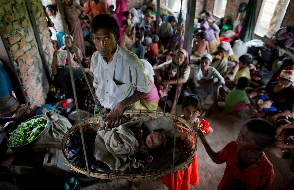 . Internally displaced Rohingya people take shelter in a building which belongs to a mosque ahead of the arrival of Cyclone Mahasen, in Sittwe, northwestern Rakhine State, Myanmar, Wednesday, May 15, 2013. A massive evacuation to clear low-lying camps ahead of a cyclone has run into a potentially deadly snag as members of the displaced Rohingya minority living there have refused to leave because they don\'t trust Myanmar authorities. (AP Photo/Gemunu Amarasinghe)