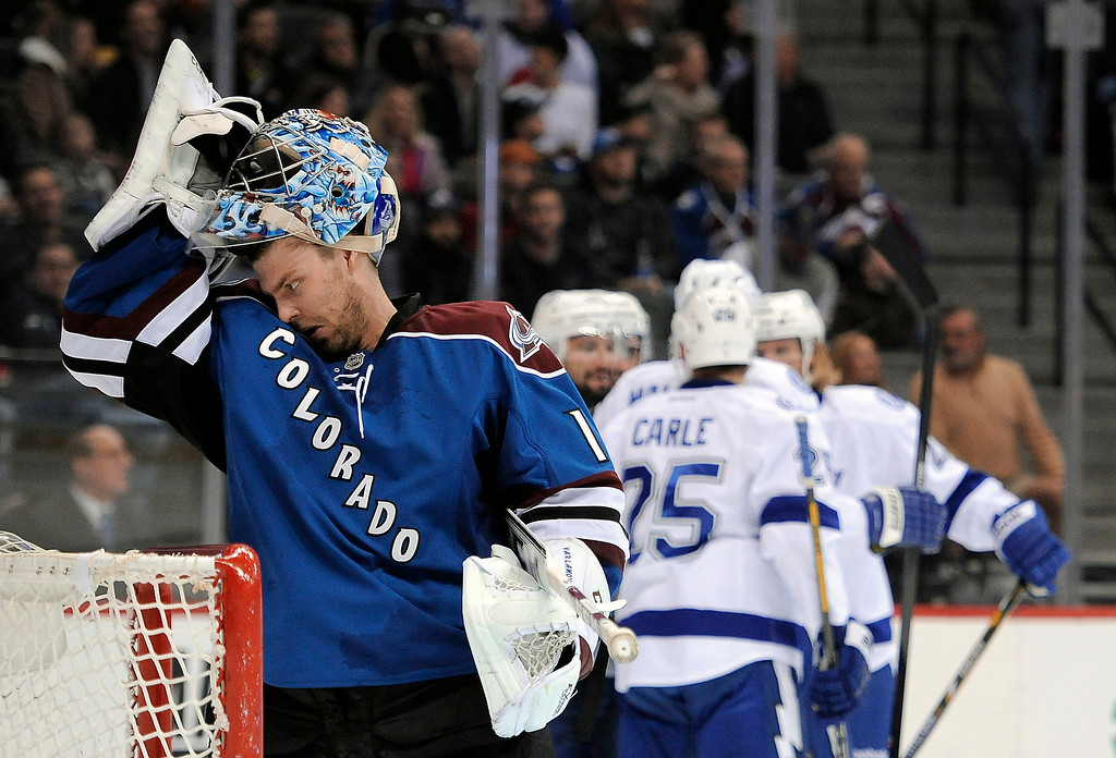 . Colorado Avalanche goalie Semyon Varlamov, left, of Russia, takes off his mask as the Tampa Lightning celebrate a goal by center Nate Thompson during the second period of an NHL hockey game Sunday, March 2, 2014, in Denver.  (AP Photo/Chris Schneider)