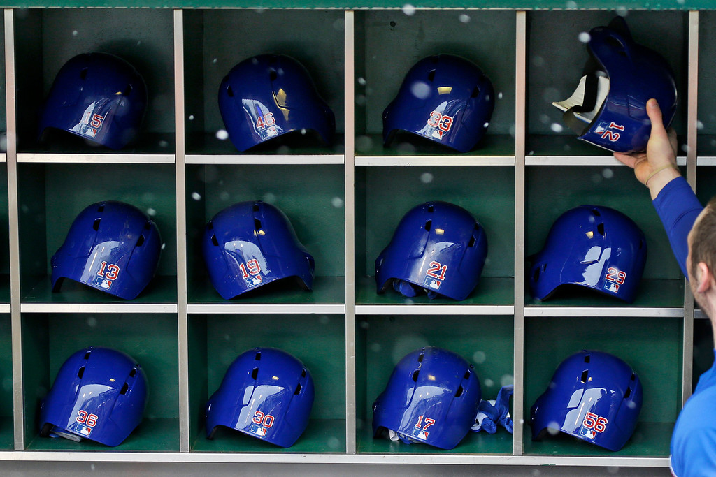 . Snow falls as a batboy places the batting helmets for the  Chicago Cubs in the dugout rack before an opening day baseball game against the Pittsburgh Pirates at PNC Park in Pittsburgh, Monday, April 1, 2013. (AP Photo/Gene J. Puskar)