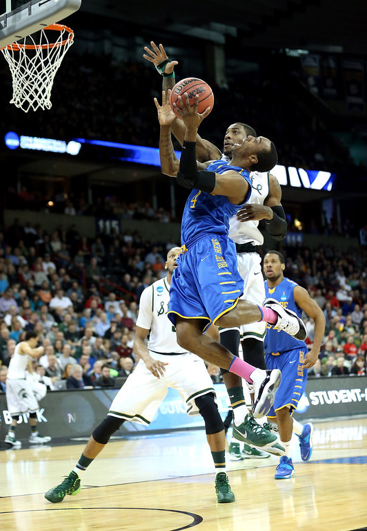 . Jarvis Threatt #4 of the Delaware Fightin Blue Hens goes up for a shot against Branden Dawson #22 of the Michigan State Spartans during the second round of the 2014 NCAA Men\'s Basketball Tournament at Spokane Veterans Memorial Arena on March 20, 2014 in Spokane, Washington.  (Photo by Stephen Dunn/Getty Images)