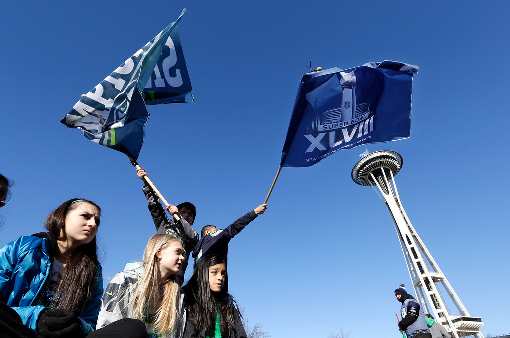. Seattle Seahawks fans cheer as they wait for the Super Bowl champions parade to begin Wednesday, Feb. 5, 2014, in Seattle. (AP Photo/Elaine Thompson)