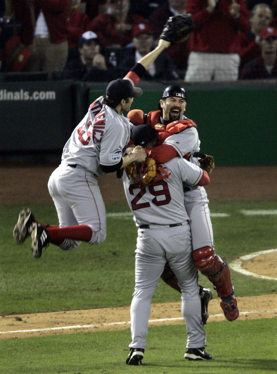 . Boston Red Sox\'s Doug Mientkiewicz, left and catcher Jason Varitek jump into Keith Foulke\'s (29) arms after the Red Sox defeated the St. Louis Caridnals 3-0 in Game 4 to win the World Series at Busch Stadium in St. Louis, Wednesday, Oct. 27, 2004.  (AP Photo/Sue Ogrocki)