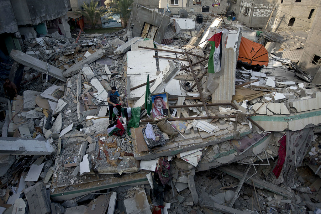 . A Palestinian man displays national flags, Islamist Hamas movement flags and portraits of Hamas top leader in Gaza, Ismail Haniya, on the rubble of the latter\'s house after it was hit by an overnight Israeli air strike, on July 29, 2014 in Gaza City. Bloodshed in and around Gaza surged with strikes killing at least 13 Palestinians, a day after five Israeli soldiers died, shattering hopes for an end to three weeks of violence. AFP PHOTO/MAHMUD  HAMS/AFP/Getty Images