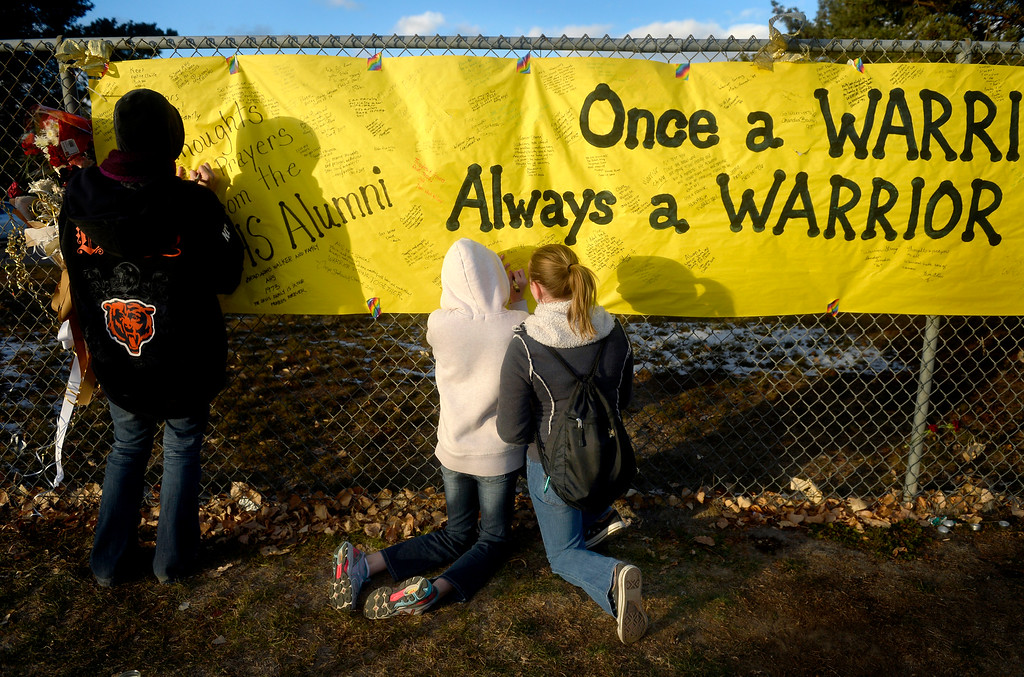. Mourners visit the memorial for shooting victim Claire Davis and write their goodbyes along a fence outside Arapahoe High School in Centennial on Dec. 22, the day after Davis\' death. Photo by Jamie Cotten, Special to The Denver Post