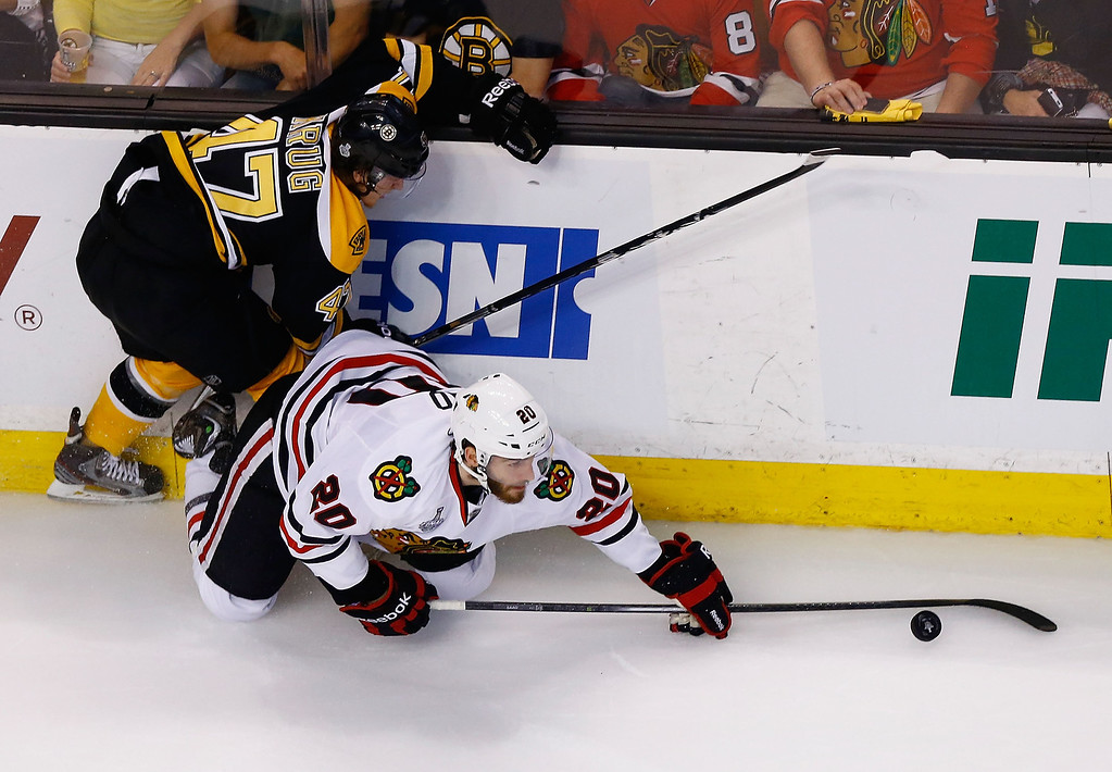 . Torey Krug #47 of the Boston Bruins and Brandon Saad #20 of the Chicago Blackhawks fight for the puck along the boards in the second period during Game Six of the Stanley Cup Final on June 24, 2013 at TD Garden in Boston, Massachusetts. (Photo by Jared Wickerham/Getty Images)