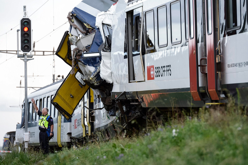 . A policeman works at the site where two passenger trains collided head-on in Granges-pres-Marnand, western Switzerland, Monday, July 29, 2013. Police say at least 44 people were injured, four of them seriously. (AP Photo/Keystone, Laurent Gillieron)