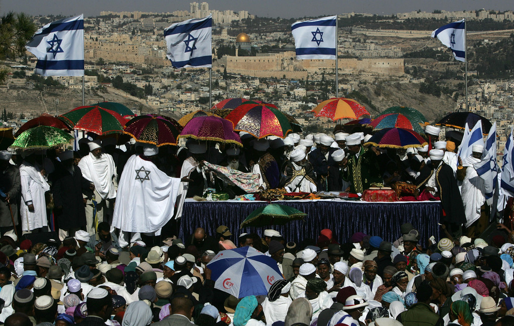 . JERUSALEM, -:  Back dropped by the old city of Jerusalem and Islam\'s golden Dome of the Rock Ethiopian Jews pray during the Sigd holiday marking the desire for \'return to Jerusalem\', as they celebrate from a hill top in Jerusalem 20 November 2006. Sigd used to mark the aspirations of Ethiopians Jews to go to Jerusalem. Today Sigd is celebrated in the holy city with thousands of Ethiopians from all over Israel congregating to pray together. The communities are led by the \'Kessim\' (top) who recites prayers while they pray overlooking the old city of Jerusalem. MENAHEM KAHANA/AFP/Getty Images