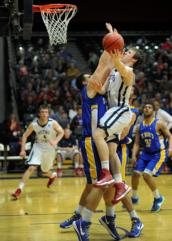 . DENVER, CO. - MARCH 19: Metro State guard Mitch McCarron (10) drove the lane on Rattlers center Kevin Kotzur (55) in the second half. The Metro State men\'s basketball team defeated St. Mary\'s (Texas) 78-70 in a RMAC playoff game Tuesday night, March 19, 2013. With the win the Roadrunners secured the South Central regional championship (Photo By Karl Gehring/The Denver Post)