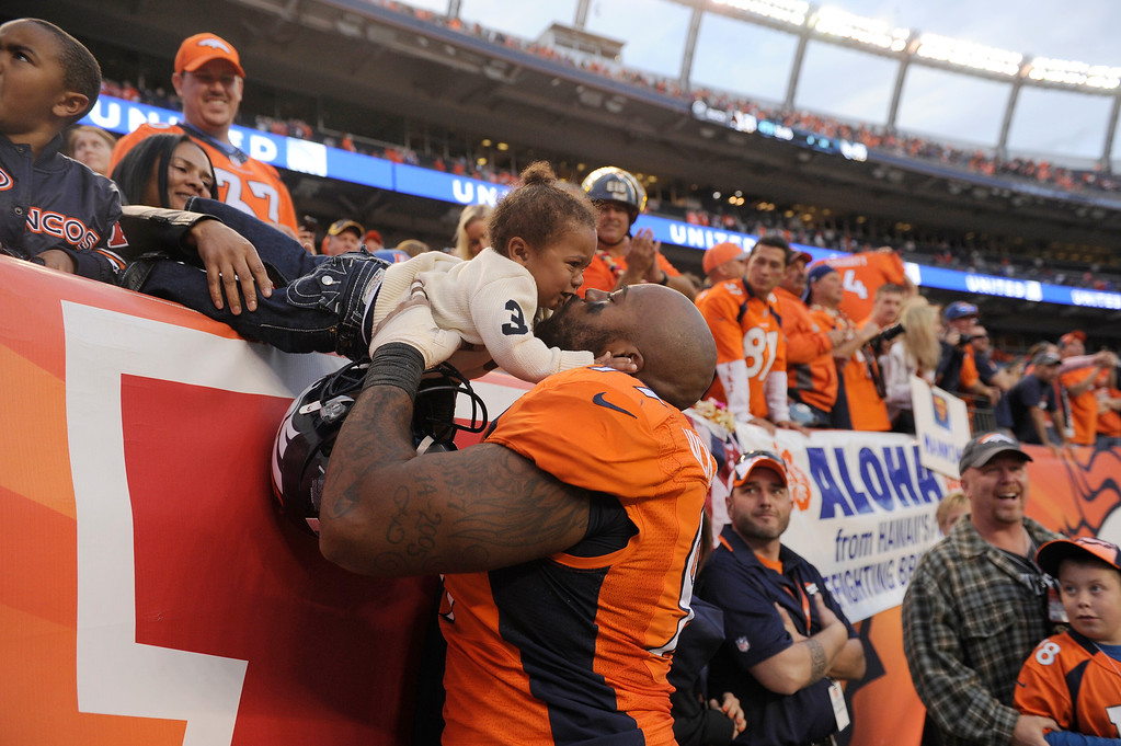 . Denver Broncos defensive tackle Kevin Vickerson (99) kisses his son Kevin Vickerson, Jr. after the game. The Denver Broncos take on the Washington Redskins at Sports Authority Field at Mile High in Denver on October 27, 2013. (Photo by Joe Amon/The Denver Post)