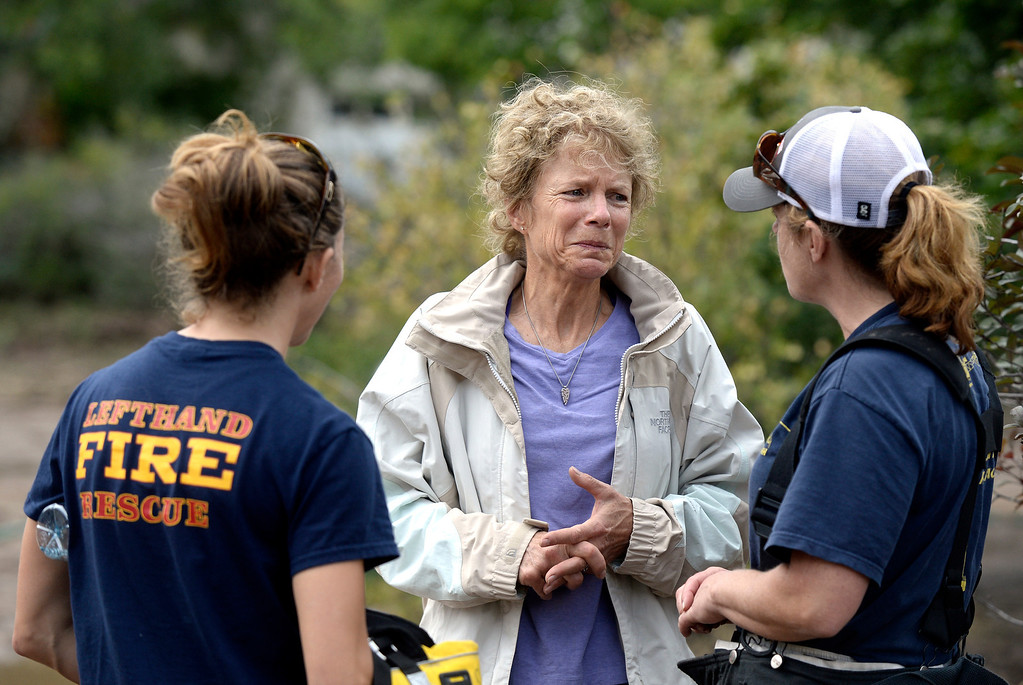 . Suzanne Sophocles, center, shows her emotions after being rescued from her flooded home, Friday, Sept. 13, 2013 in Boulder, Colo. By truck and helicopter, thousands of people stranded by floodwaters came down from the Colorado Rockies on Friday, two days after seemingly endless rain turned normally scenic rivers and creeks into coffee-colored rapids that wrecked scores of roads and wiped out neighborhoods. (AP Photo/The Daily Camera, Jeremy Papasso) NO SALES