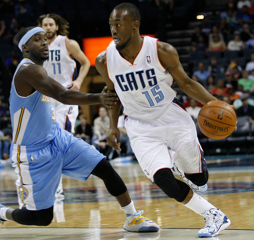 . Charlotte Bobcats guard Kemba Walker, right, drives around Denver Nuggets guard Ty Lawson during the first half of an NBA basketball game in Charlotte, N.C., Monday, March 10, 2014. (AP Photo/Nell Redmond)