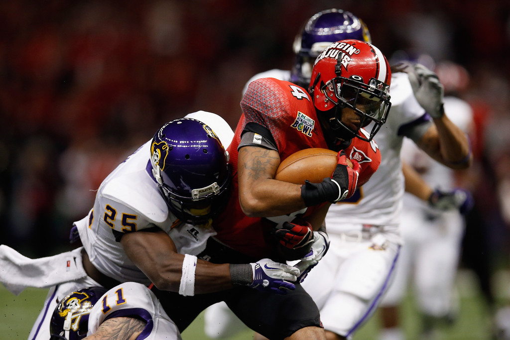. Javone Lawson #4 of the Louisiana-Lafayette Ragin Cajuns is tackled by Leonard Paulk #25 of the East Carolina Pirates during the R+L Carriers New Orleans Bowl at Mercedes-Benz Superdome on December 22, 2012 in New Orleans, Louisiana.  (Photo by Chris Graythen/Getty Images)